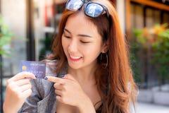 Finger hermoso atractivo de la demostración y del punto de la mujer a la tarjeta de crédito fotos de archivo
