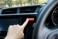 Finger hitting car emergency light botton in car. Finger hitting car emergency light button in car on nature background Royalty Free Stock Photos