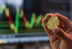 Finger holding bitcoin and chart market stock background, business concept, selective focus. stock photos
