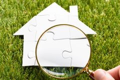 Finger Holding Magnifying Glass Over Puzzle House Stock Photos