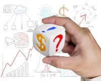 Finger holding white dice Stock Images