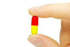Finger holds pill Royalty Free Stock Image