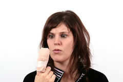 The Finger Hurts. A young woman is looking in pain at her finger that hurts Stock Images