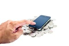 Finger im Presse-Handy auf Münzen Lizenzfreie Stockfotografie