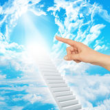 Finger indicates stairway to heaven. With clouds and sun. Concept background Stock Images