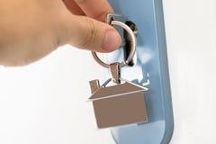Finger Inserting Key In Keyhole Stock Photo