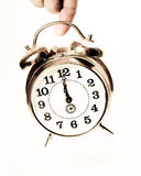 Finger keep old clock on white background. Studio shot in retro style Royalty Free Stock Photos