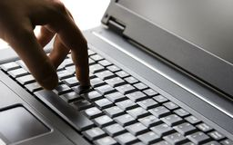 Finger on key. A hand press a key on a laptop keyboard Stock Images