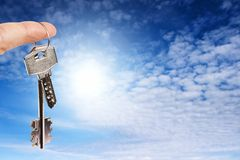 Finger with keys. On blue sky background Royalty Free Stock Images