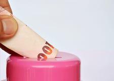 Finger lässt thailändische Banknote im rosa Sparschwein für die Rettung fallen Stockfoto