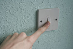 Finger on a light switch. A man pressing the button of a light switch Stock Photos