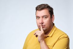 Finger on lips as man gesturing shh sign. Fat caucasian guy ask to be silent Royalty Free Stock Photography