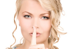 Finger on lips. Bright picture of young woman with finger on lips Stock Photos