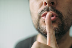 Finger on lips, man gesturing shhh sign Stock Image