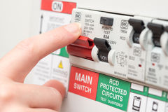 Finger on MAIN Switch on RCD Circuit Breaker Board Royalty Free Stock Image