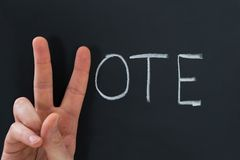 Finger making v sign with the word vote Royalty Free Stock Image