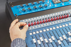 Finger of a man turning the knobs of audio console Royalty Free Stock Photography