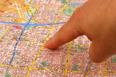 Finger on a map Stock Photo