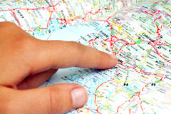 Finger on the map. Finger pointing to the location map Stock Photos