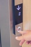 Finger masculino que aprieta el botón del elevador de la flecha Foto de archivo libre de regalías