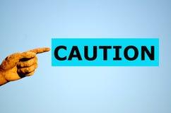 Finger med ljus - blå etikettVARNING Arkivfoton