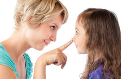 Finger of mother on nose of daughter Stock Images