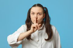 Finger on mouth. Fun girl on blue background show silence gesture close her mouth with finger Stock Images