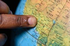 Finger negro que señala Nigeria en un mapa Fotos de archivo libres de regalías