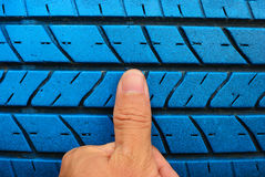 Finger with old blue tire Stock Photos
