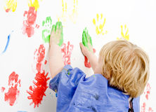 Finger paingint. Young boy finger painting on a wall stock photos