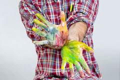 Finger paint. Man spreading hands with water colors Royalty Free Stock Photo