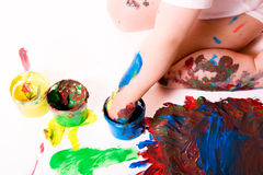 Finger Painting. Child painting with his hands using several color cans. White background stock image