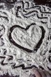Finger painting of heart on the flour stock illustration