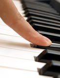 Finger and piano Stock Photos