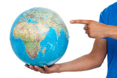 A finger pointing at the globe. closeup shot royalty free stock images