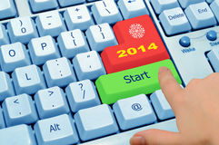 Finger pointing at the green key start 2014. Finger pointing at the green button of computer keyboard Royalty Free Stock Photos