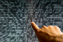 Finger pointing at a red bit in binary code Stock Image