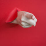 Finger pointing through red paper Stock Photo