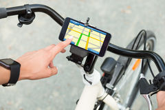 Finger Pointing At Smart Phone Showing GPS Navigation. Close-up Of Human Hand Pointing At Smart Phone Showing GPS Navigation On Bicycle stock image
