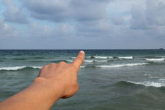 Finger pointing somewhere. At the sea stock photos