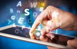 Finger pointing on tablet pc, letters concept Stock Photo