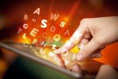 Finger pointing on tablet pc, letters concept Stock Images