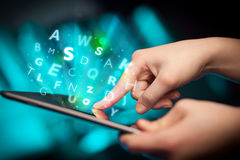Finger pointing on tablet pc, letters concept Royalty Free Stock Photography