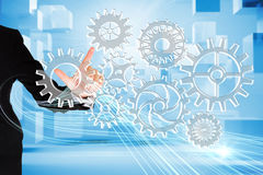 Finger pointing to cogs and wheels Stock Photos