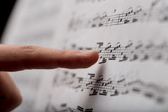 Finger pointing to music score. Index finger on foreground pointing out some musical notes on a music score paper, over a black blurred background of a concert Royalty Free Stock Image