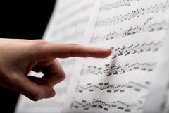 Finger pointing to music score. Index finger on foreground pointing out some musical notes on a music score paper, over a black blurred background of a concert Royalty Free Stock Photos