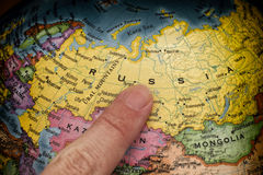 Finger pointing to Russia on a globe Stock Image