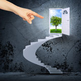 Finger pointing to spiral stairs. And magic doors Stock Photos