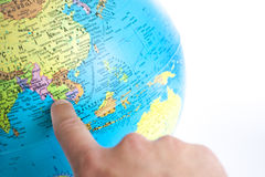 A Finger pointing to Thailand in a World Globe Stock Photo