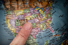 Finger pointing to USA on a globe Royalty Free Stock Photos